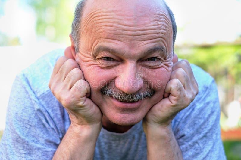 Portret piękny starsza osoba mężczyzna Kłama na trawie uśmiechniętej i patrzeje kamerę obrazy royalty free