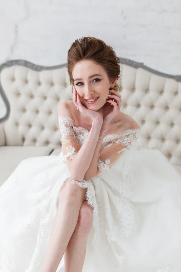 Portret piękny szczęśliwy panny młodej obsiadanie na kanapie, zakończenia vertical strzał zdjęcie stock