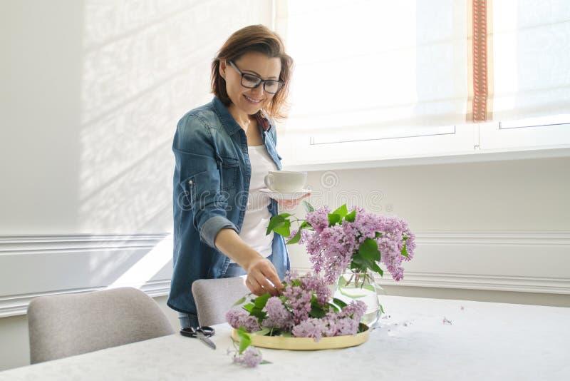 Portret pi?kna dojrza?a kobieta z bukietem lili kwiaty w domu T?o ?omota blisko okno domowy wn?trze obrazy royalty free