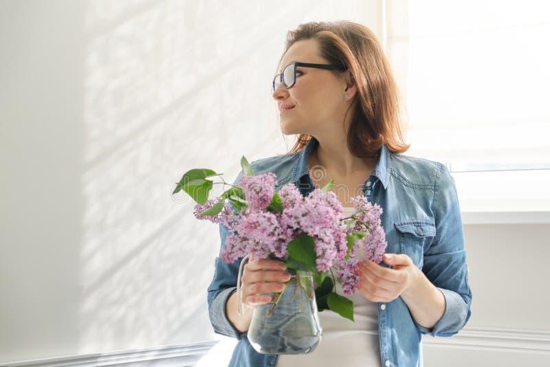 Portret pi?kna dojrza?a kobieta z bukietem lili kwiaty w domu T?o ?omota blisko okno domowy wn?trze zdjęcie royalty free