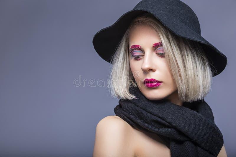 Portret Pi?kna Kaukaska Blond dziewczyna w czarnym kapeluszu Nad Szarym t?em z Twarzowym makija?em fotografia royalty free