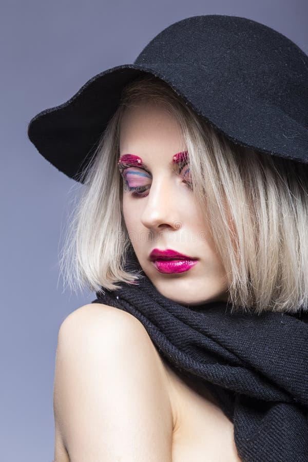 Portret Pi?kna Kaukaska Blond dziewczyna w czarnym kapeluszu Nad Szarym t?em z Twarzowym makija?em obrazy stock