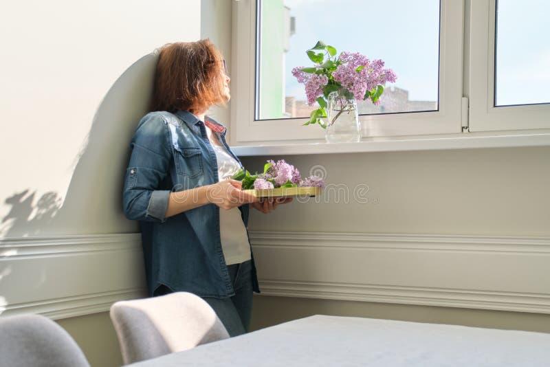 Portret pi?kna w ?rednim wieku kobieta z bukietem lili kwiaty w domu T?a ?wiat?a ?ciany ?wiat?o s?oneczne w okno zdjęcia stock
