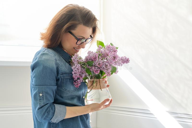 Portret pi?kna w ?rednim wieku kobieta z bukietem lili kwiaty w domu T?a ?wiat?a ?ciany ?wiat?o s?oneczne w okno obrazy royalty free