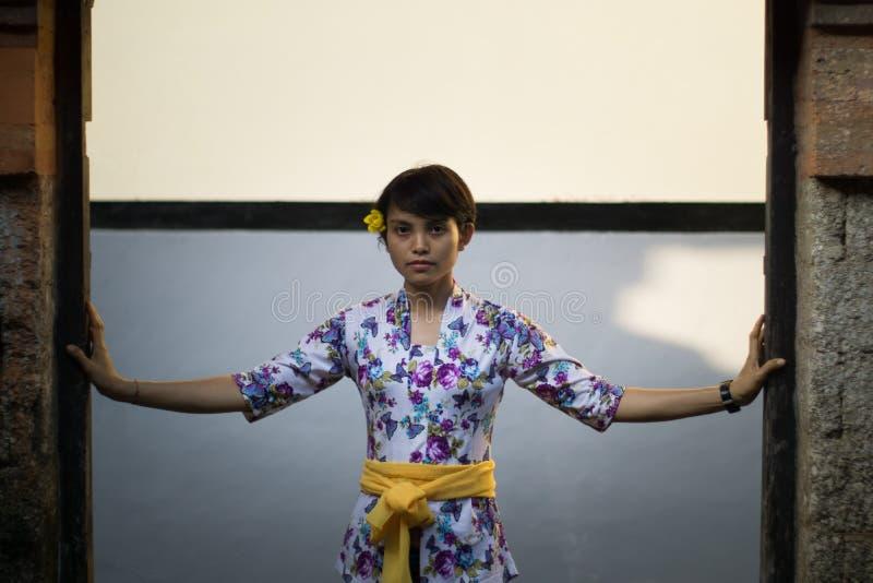 Portret pi?kna z w?osami kobieta z kwiatem na jego ucho Jest ubranym Bali sukni? z kwiecistymi motywami, pozuje z zdjęcia royalty free
