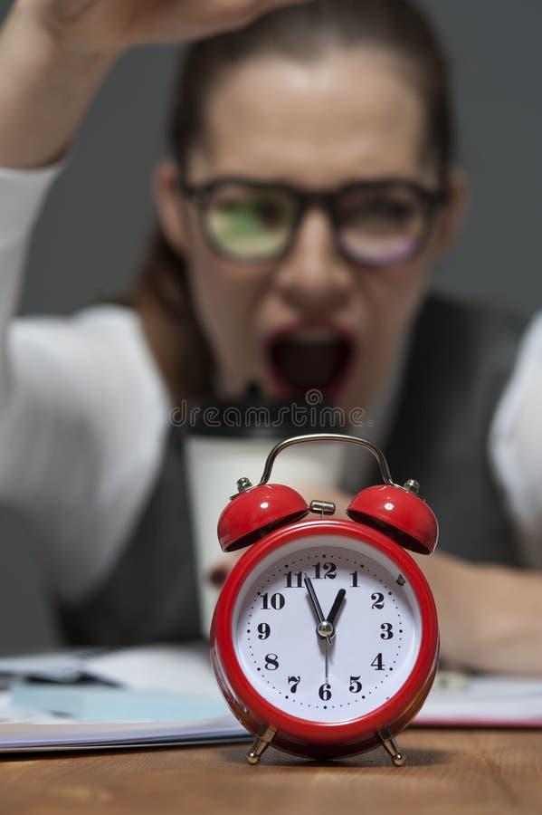 Portret ?piesz?cy m?ody bizneswoman ooking przy czerwonym retro projektuj?cym zegarem zdjęcia royalty free