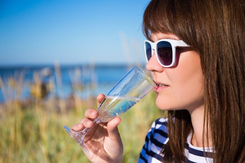 Portret pije szampana na plaży piękna kobieta obraz stock