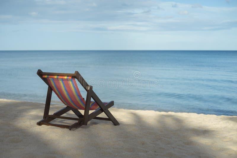 Portret plażowy krzesło na białej piasek plaży z niebieskim niebem i błękitnym morzem, selekcyjna ostrość, filtrujący wizerunek,  zdjęcia royalty free