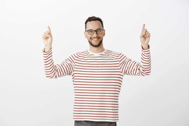 Portret podnosi palce wskazujących i wskazuje up życzliwy atrakcyjny męski sąsiad w modnych szkłach, ono uśmiecha się zdjęcia royalty free
