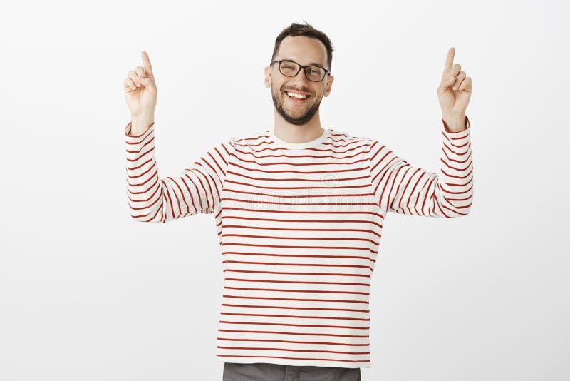 Portret podnosi palce wskazujących i wskazuje up życzliwy zrelaksowany europejski brodaty mężczyzna w czarnych szkłach, ono uśmie zdjęcie stock
