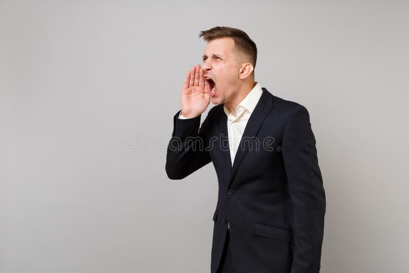 Portret podrażniony młody biznesowy mężczyzna w klasycznym czarnym kostiumu, koszulowy krzyczeć z ręka gestem odizolowywającym na obrazy royalty free