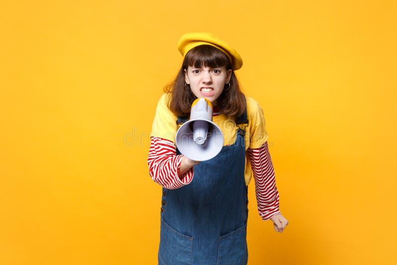 Portret podrażniony dziewczyna nastolatek w francuskim berecie, drelichowi sundress krzyczy w megafonie odizolowywającym na kolor zdjęcia stock