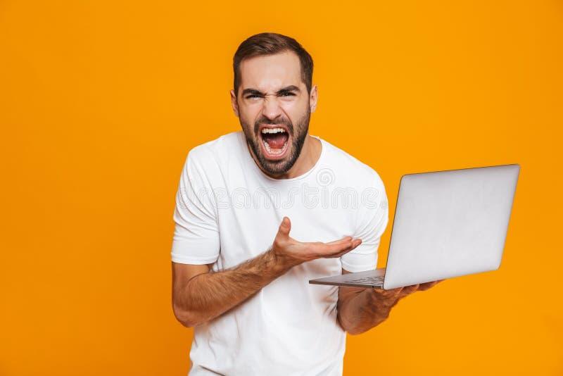 Portret podrażniony mężczyzna 30s w białej koszulce krzyczy srebnego laptop i trzyma, odizolowywający nad żółtym tłem obraz royalty free