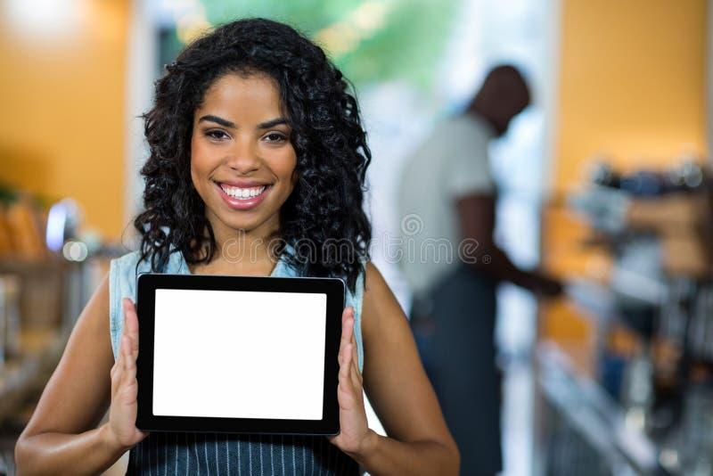 Portret pokazuje cyfrową pastylkę uśmiechnięta kelnerka obrazy stock