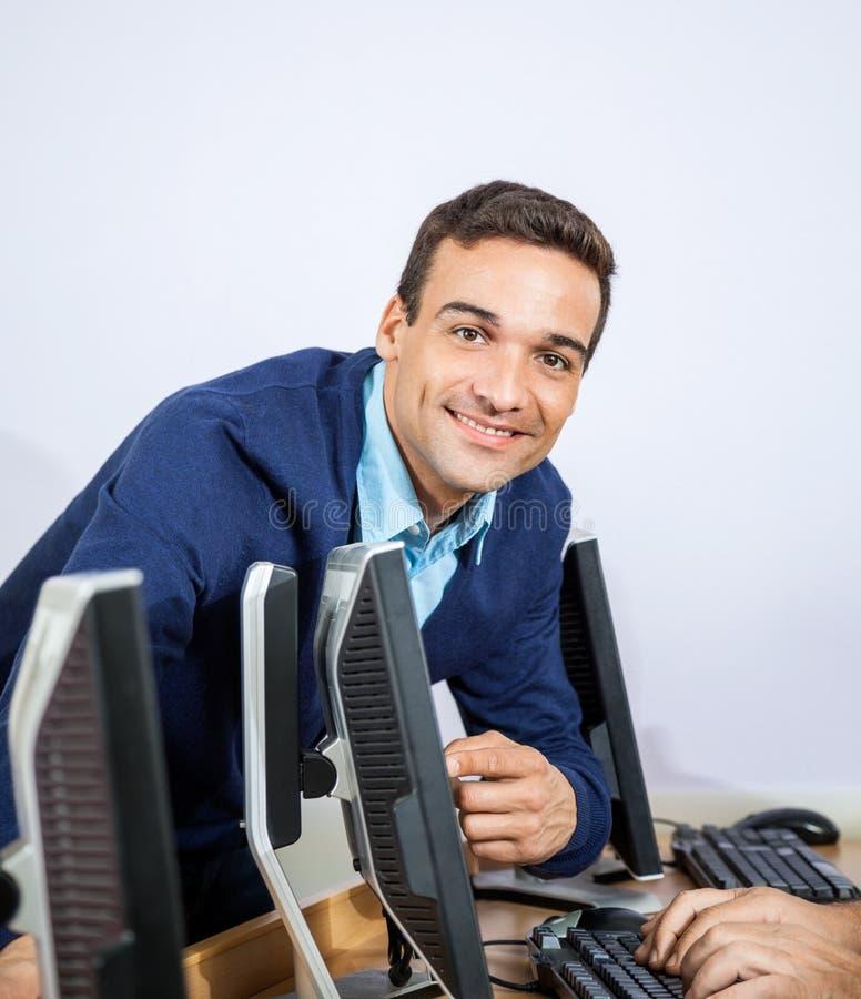 Portret Pomaga Starszego ucznia Przy Komputerowym d Szczęśliwy nauczyciel obraz stock