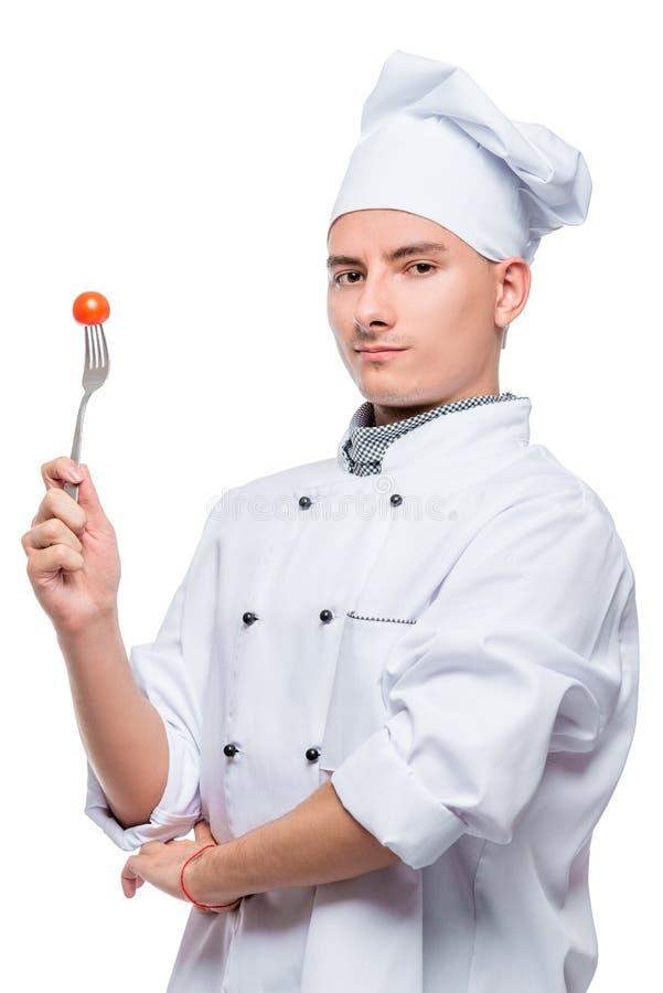 portret pomyślny profesjonalisty kucharz z czereśniowym pomidorem na rozwidleniu, strzał na białym tle obraz stock