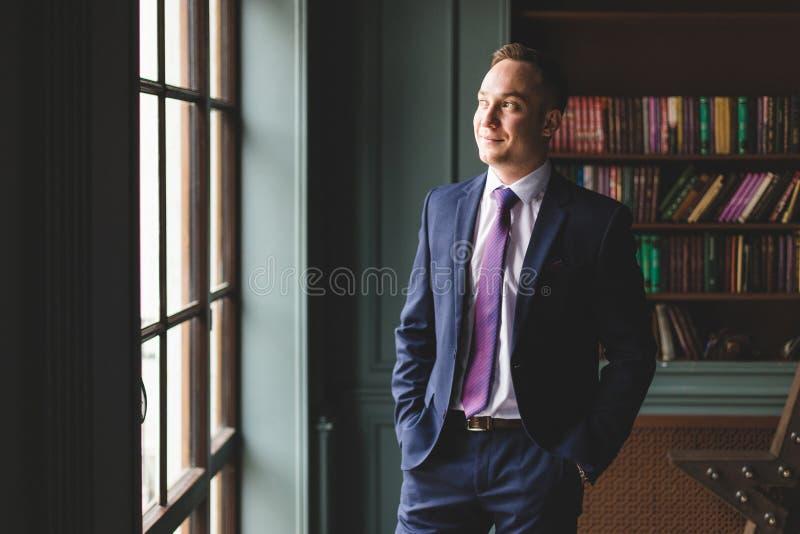 Portret pomyślna biznesmen pozycja w drogim garniturze blisko okno w jego ono uśmiecha się i biurze obraz stock