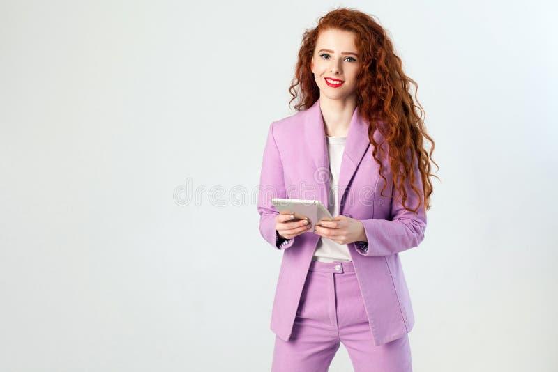 Portret pomyślna szczęśliwa piękna biznesowa kobieta z czerwonobrunatnym włosy i makeup w menchiach nadajemy się mienie pastylkę, obrazy stock
