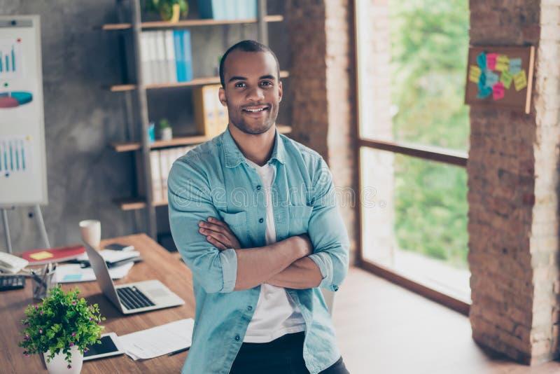 Portret pomyślny czarny facet, patrzejący kamerę, stoi z krzyżować rękami przy jego miejscem pracy w biurze w przypadkowym sma, zdjęcie royalty free
