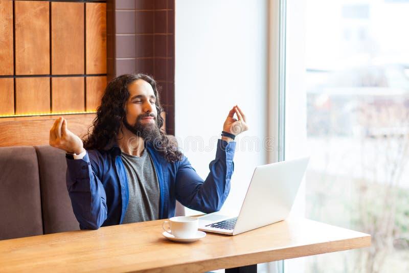 Portret pomyślny przystojny młody dorosły mężczyzny freelancer w przypadkowego stylu obsiadaniu w kawiarni z laptopem, mienie ręk zdjęcie stock