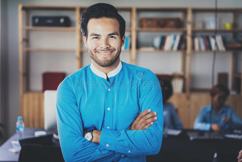 Portret pomyślny ufny latynoski biznesmen ono uśmiecha się przy kamerą w nowożytnym biurze Horyzontalny, zamazany obrazy royalty free