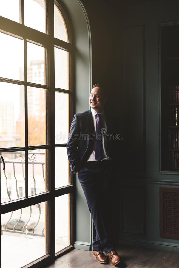 Portret pomy?lna biznesmen pozycja w drogim garniturze blisko okno w jego ono u?miecha si? i biurze obraz royalty free