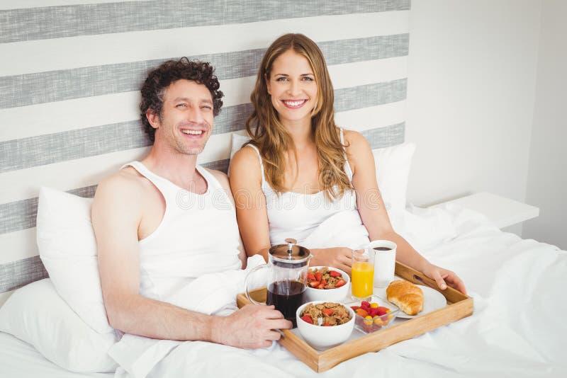 Portret potomstwa dobiera się mieć śniadanie na łóżku fotografia stock