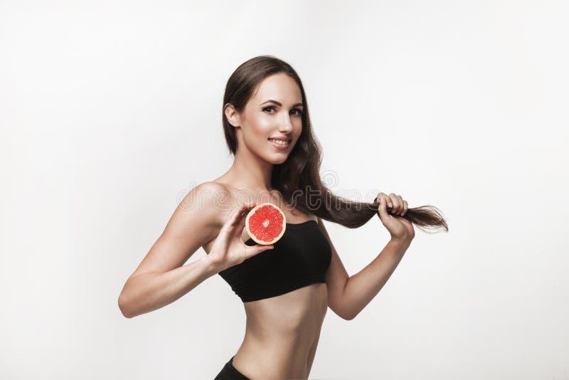 Portret potomstwa dostosowywał kobiety trzyma różowy grapefruitowego fotografia stock
