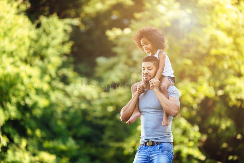 Portret potomstwa ojcuje nieść jego córki na jego z powrotem zdjęcie stock