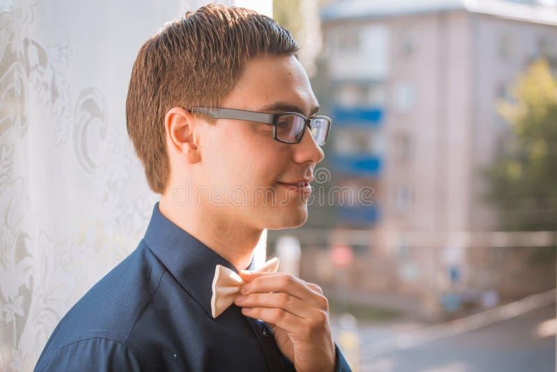 Portret potomstwa przygotowywa wiązać łęku krawat podczas gdy dostawać przygotowywający dla poślubiać fotografia stock