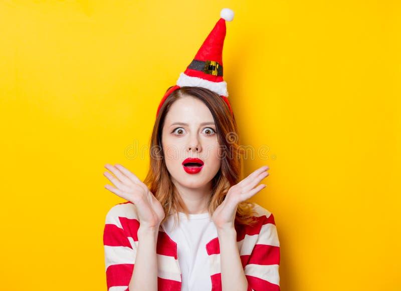 Portret potomstwa zaskakiwał rudzielec kobiety w Święty Mikołaj kapeluszu zdjęcie stock