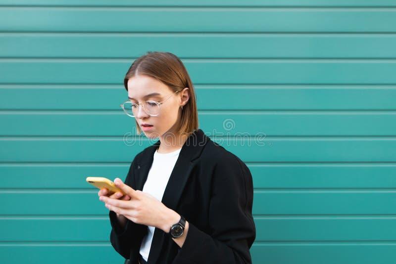 Portret poważna kobieta w szkłach i kurtce, używa smartphone na tle turkus ściana obrazy royalty free