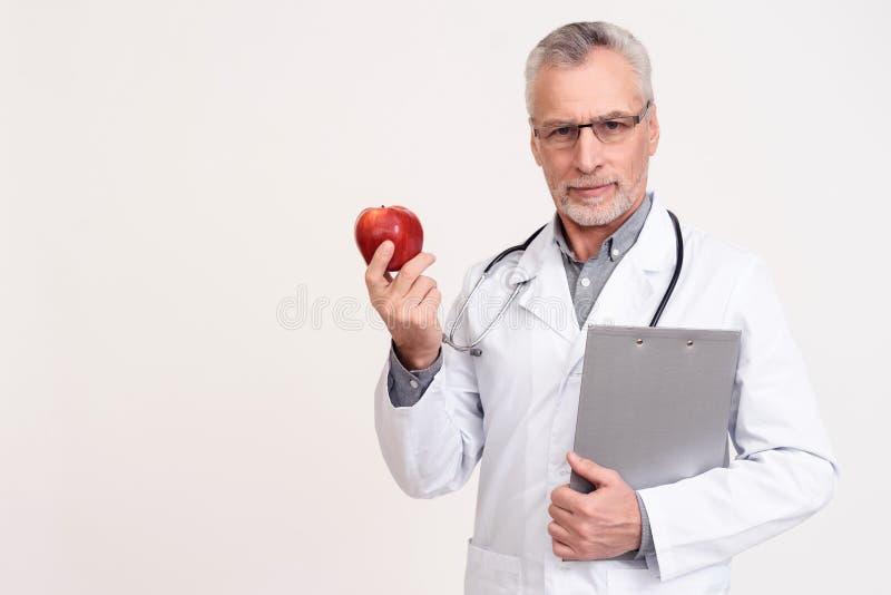 Portret poważna lekarka z stetoskopu i schowka mienia jabłkiem odizolowywającym fotografia royalty free