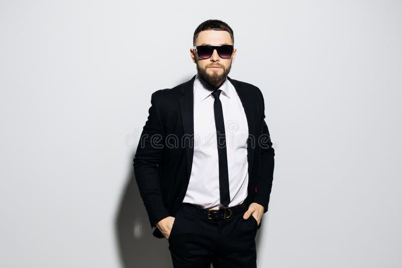 Portret poważna potomstwo mody mężczyzna pozycja z jego rękami w jego kieszeniach i patrzeć w kamerę podczas gdy będący ubranym o fotografia stock