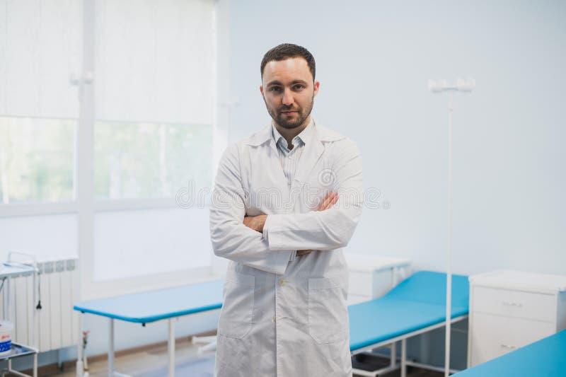 Portret poważna ufna samiec lekarki pozycja z rękami krzyżował przy medycznym biurem fotografia royalty free