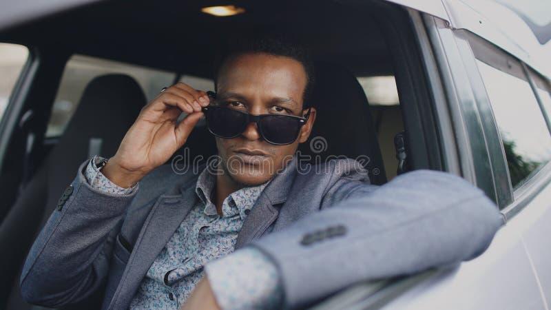 Portret poważny biznesmena obsiadanie wśrodku samochodu stawiającego okulary przeciwsłoneczni i ono uśmiecha się outdoors w kamer zdjęcia stock