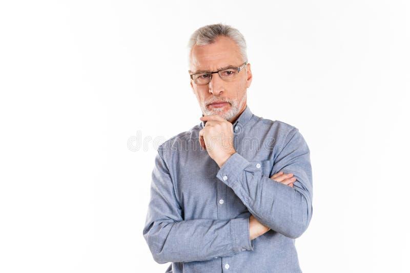 Portret poważny ufny mężczyzna patrzeje na boku z fałdowymi rękami obrazy stock