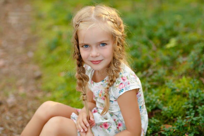 Portret powabna dziewczyna z blondynek pigtails na trawie wewnątrz, obrazy stock