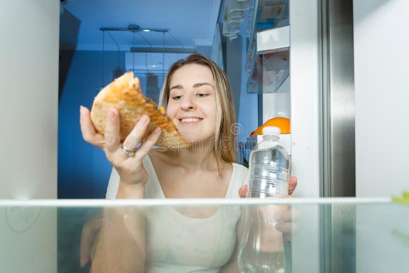 Portret powalać głodny przy nocą wybiera między kalorii pizzą i butelką woda młoda kobieta zdjęcie stock