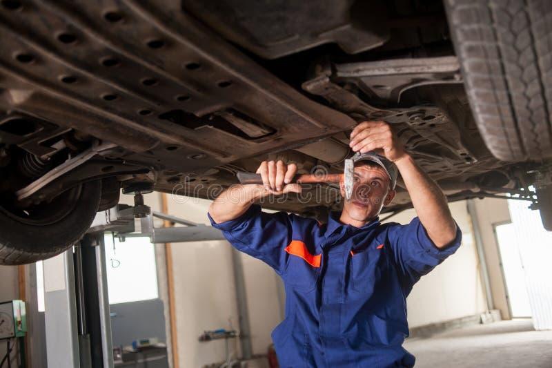 Portret pracuje z narzędziami pod samochodem samochodowy mechanik zdjęcia stock