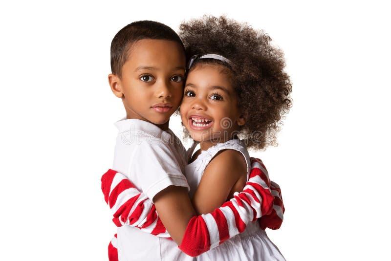 Portret preschool afroamerykańscy rodzeństwa ściska each inny odosobniony zdjęcie stock