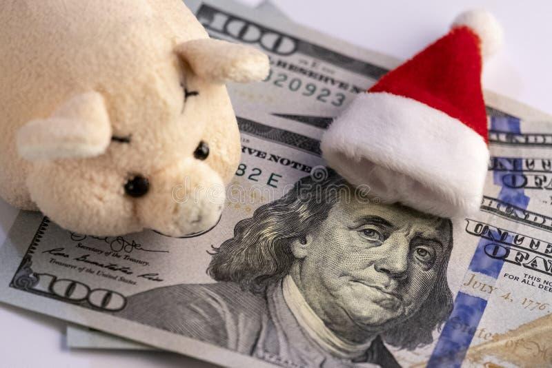 Portret prezydent stanów zjednoczonych na sto dolarowych rachunkach, na których kłama czerwoną nakrętkę Święty Mikołaj Gotówkowy  obraz stock