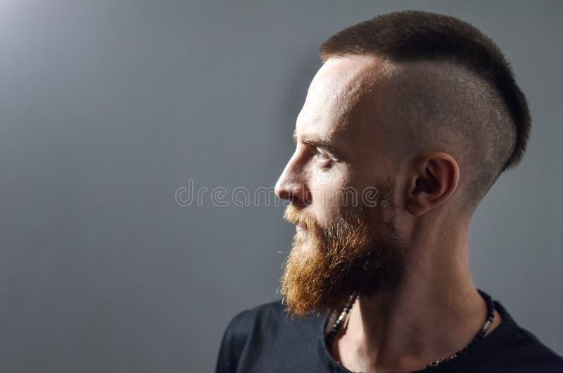 Portret Profil młody człowiek z czerwoną brodą na szarym tle Mohawk fryzura, iroquois, mohican obrazy stock