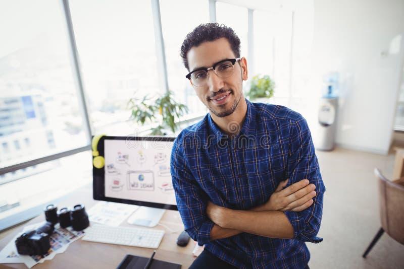 Portret projektant grafik komputerowych pozycja z rękami krzyżował przy biurkiem obraz stock