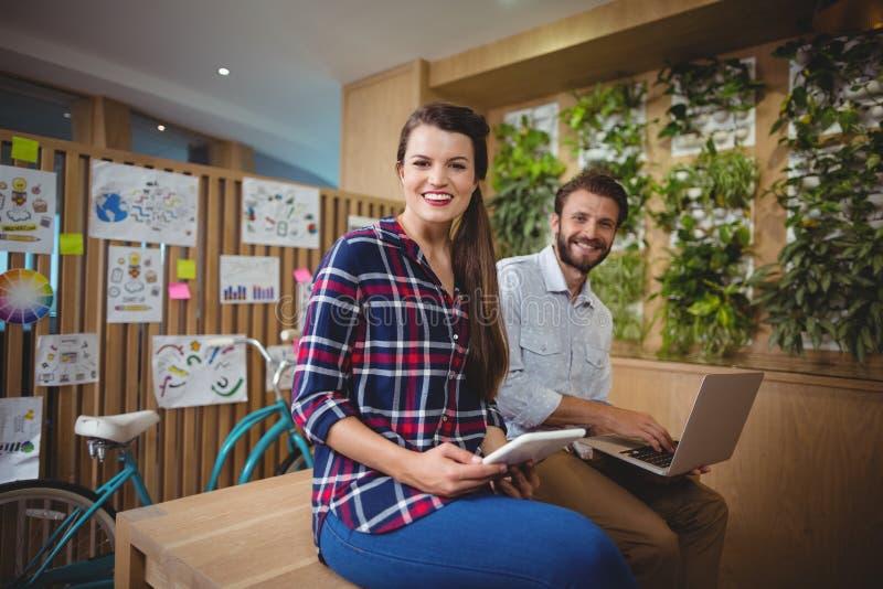 Portret projektant grafik komputerowych siedzi na biurku używać laptop i cyfrową pastylkę fotografia royalty free