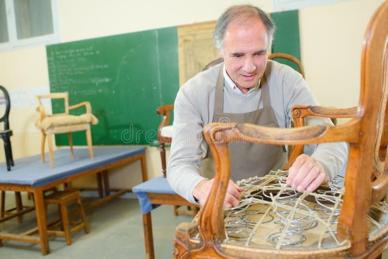 Portret przechodzić na emeryturę mężczyzna pozycję przy warsztatem i działaniem obrazy royalty free