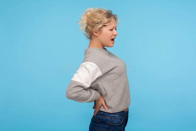 Portret przepracowanej niezdrowej dorosłej kobiety z kręconymi włosami w bluzie z bólem pleców, uszkodzonym tarczą kręgosłupa obrazy stock