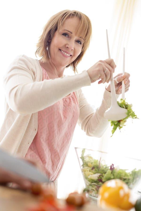 Portret przygotowywa sałatkowego puchar przy kuchnią uśmiechnięta kobieta obraz stock