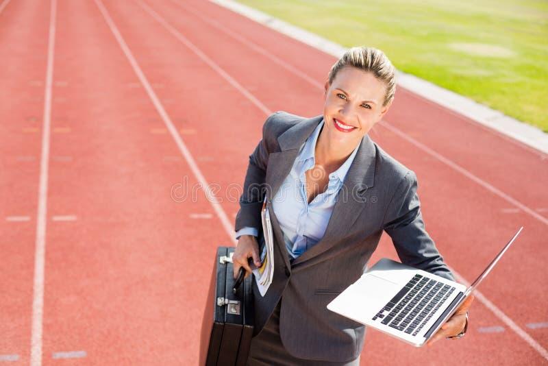 Portret przygotowywający biegać z teczką i laptopem szczęśliwy bizneswoman fotografia stock