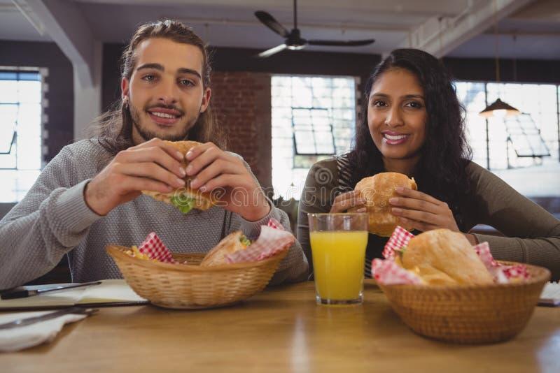 Portret przyjaciele ma hamburgery przy kawiarnią zdjęcie stock
